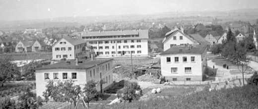 Le «nouveau camp» au début des années cinquante: Au premier plan à gauche le bâtiment des gardes. A droite le bloc I des détenus avec encore le toit plat d'origine. Derrière les blocs II et III (surélevés entre-temps). A la fin de la guerre, le bâtiment transversal n'avait qu'un étage et était encore en chantier.